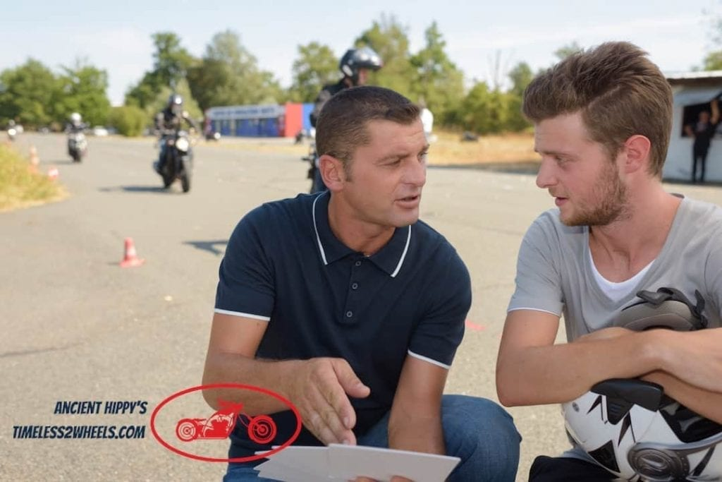 Motorcycle instructor talking to young man